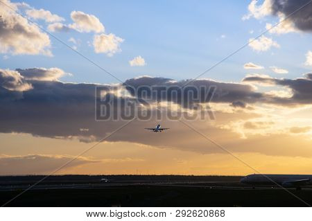 Passanger Airplane Flying Up In Front Of Bright Dusk