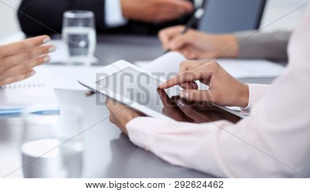 Woman Hands Using Tablet At Meeting. Business People Group Working Together In Office, Close-up. Neg