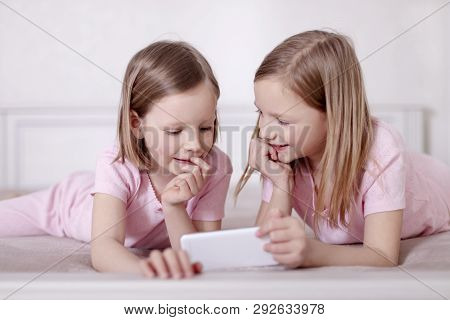 Two Little Girls (sisters) In Pink Pajamas On The Bed Watching A Smartphone And Reading An E-book. S