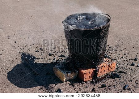 Molten hot tar in a bucket on the bricks. Roof repair. Smoke from the bucket poster