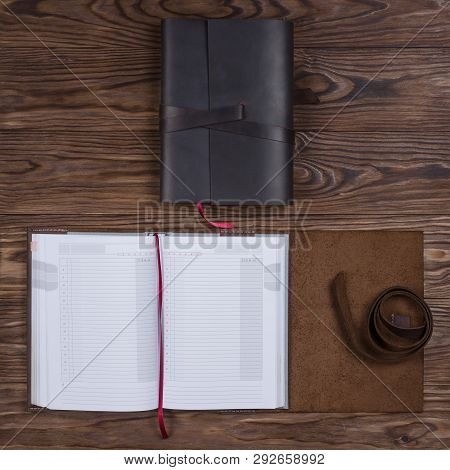 Black And Brown Opened Handmade Leather Notebook Cover With Notebook Inside On Wooden Background. St