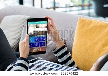 Smart Home Automation Control Concpet.woman Lying Down On Sofa Using Tablet Control Device In Home.d