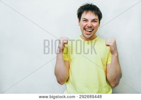 Excited overjoyed man feel happy looking at camera, euphoric winner screaming with joy celebrating win victory success triumph isolated at white grey studio background poster