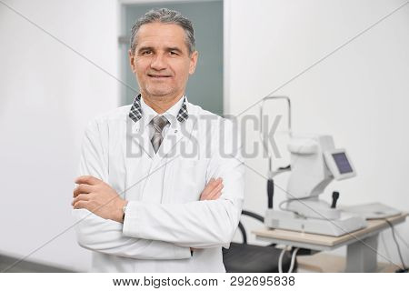 Doctor Ophthalmologist Wearing In White Medical Coat Standing In Medical Room Of Clinic. Eye Special