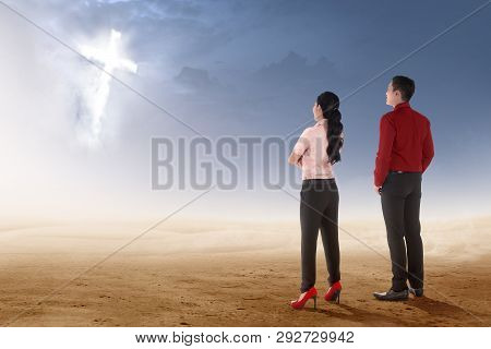 Rear View Of Two Asian Business People Standing On Desert And Looking At Glowing Christian Cross On