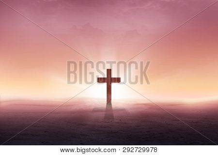 Christian Cross On The Desert With Sun Rays Over Sunrise Background