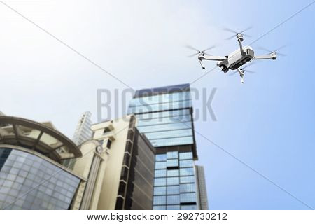 White Drone With Camera Flying To The Top Of Modern Building With Blue Sky Background