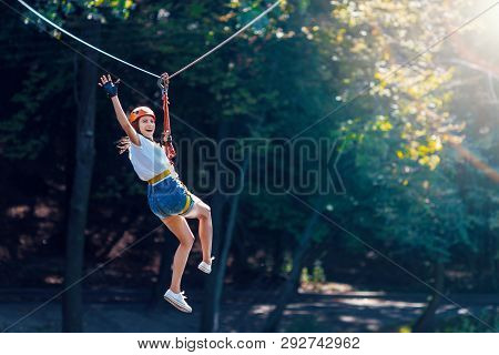 Closeup Of Female Slender Legs In White Sneakers Keep Balance On Wooden Stumps Hanging On Ropes On T