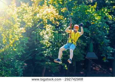 Happy Men Boy Male Gliding Climbing Down In Extreme Road Trolley Zipline In Forest On Carabiner Safe