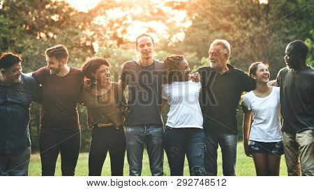 Cheerful diverse people huddling in the park
