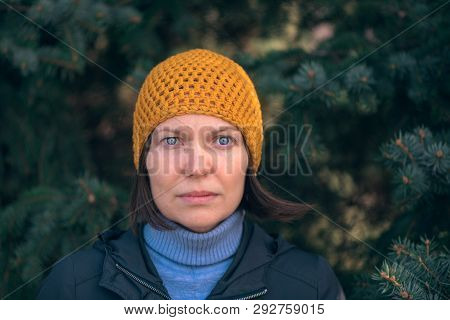 Beautiful woman in 40s headshot portrait in park, relaxed casual female person with yellow cap posing in front of fir tree on sunny spring day. poster