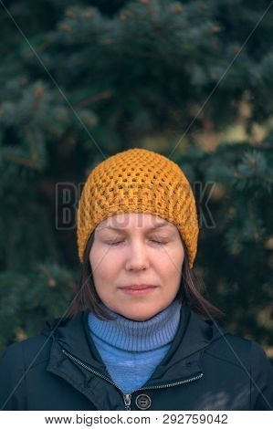 Beautiful woman in 40s headshot portrait in park with eyes closed, relaxed casual female person with yellow cap posing in front of fir tree on sunny spring day. poster