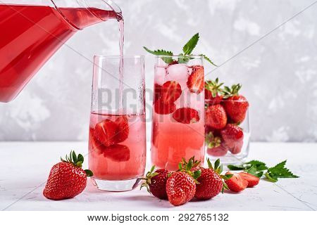 Berry Lemonade Pouring From Jug Into Glass On White Background. Cocktail With Strawberry, Ice And Mi