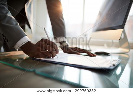 Hand of young African-american businessman with pen putting his signature on contract or other financial document