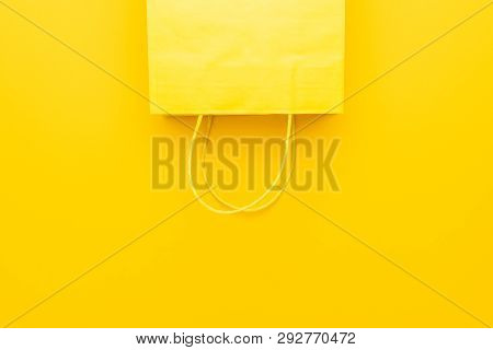 Shopping Paper Bag On The Yellow Background. Yello Shopping Bag With Copy Space. Minimalist Flat Lay