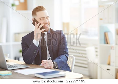 Successful elegant director or ceo of business or financial organization talking to partner on the phone in office