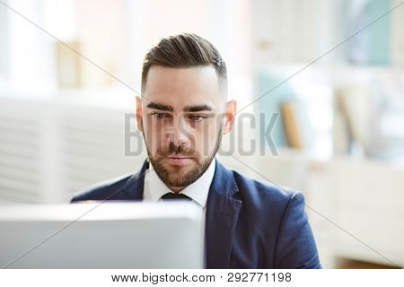 Young serious businessman concentrating on computer work while sitting in front of monitor in office