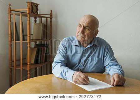 Old Man Writing Notes Or Deciding Whether To Sign A Paper Document On The Table In Front Of Him As H