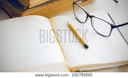 Things on the desktop that are needed to study the scientific material: ancient encyclopedias, notebook, yellow pencil and glasses poster