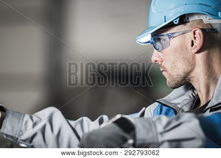 Metalwork Industry Worker In Blue Hard Hat And Safety Glasses. Industrial Theme.