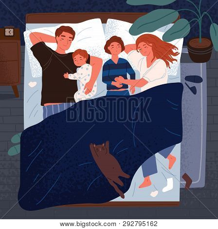 Mother, Father And Children Sleeping Together On One Bed. Mom, Dad And Kids Embracing Each Other And