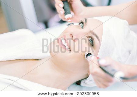 Cosmetology. Procedures on the face. Smiling girl on the procedure of microcurrent and ultrasound therapy poster