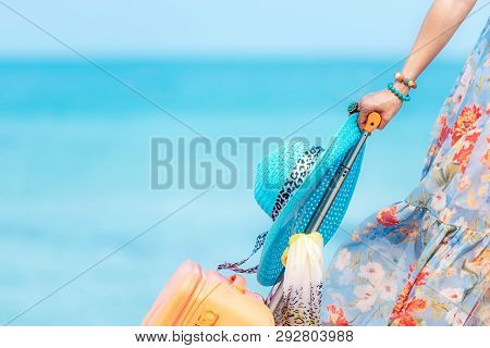 Travel Plan. Hand Women Traveler Holding Orange Luggage Walking On The Beach.  Traveler And Tourism