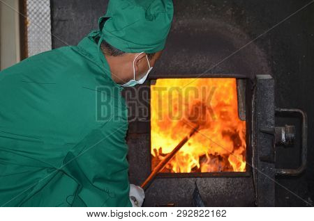 Man In Green Coat Is Working With Incinerator