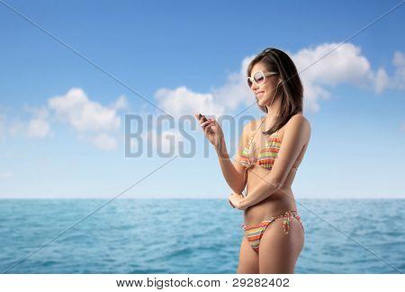 Beautiful woman in bikini at the seaside using a mobile phone