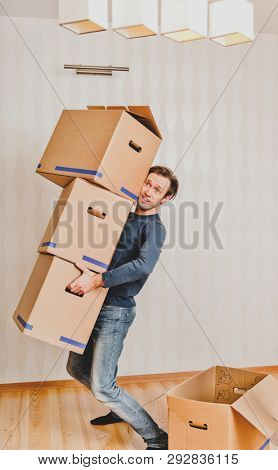 Man holding a stack of cardboard boxes. He is moving in new home.
