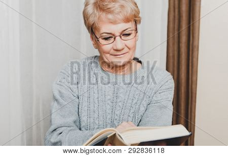 Senior woman is reading book in home. Leisure time on retirement.