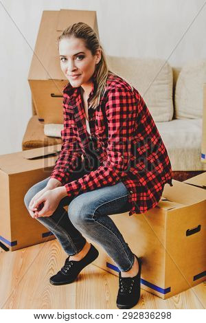 Blond woman sitting on cardboard box. She moving in new apartment.