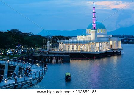 Kuching, Malaysia - March 15, 2019: Night View Of Illuminated Floating Mosque And People Walking By