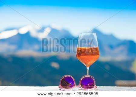 Spritz Aperol Drink By A Pool With A Lake And Mountains Background. Traditioanal Italian Aperitif.