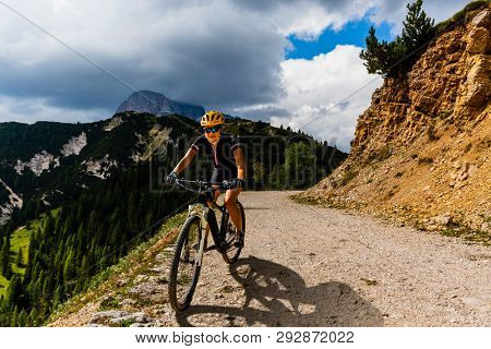 Woman cycling on electric bike on mountain trail. Woman riding on bike in Dolomites mountains landscape. Cycling e-mtb enduro trail track. Outdoor sport activity.