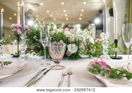 Closeup Table Setting With Plates And Tableware, Adorned With Flowers. Floral Decoration For Wedding