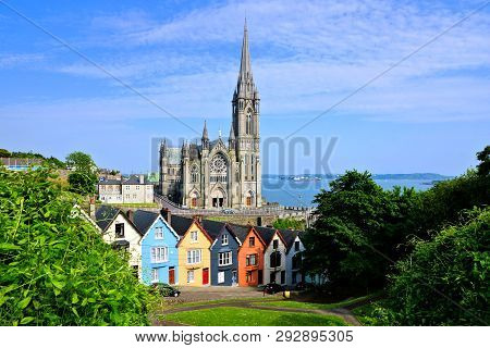Colorful Row Houses With Towering Cathedral In Background In The Port Town Of Cobh, County Cork, Ire