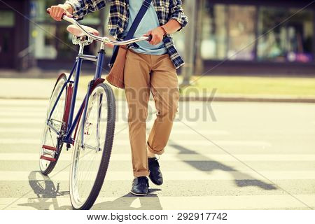 people, style, city life and lifestyle - young hipster man with shoulder bag and fixed gear bike and shoulder bag crossing crosswalk on street