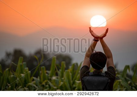 Asian Man In Corn Field Raising His Arms Holding The Sun At Sunset In Summer Solstice Day. Hope And