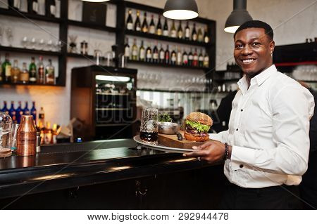 Young African American Waiter Man Hold Tray With Burger At Bar Of Restaurant.