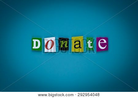 Word Donate Of Cut Letters On Blue Background. Donation Concept. Headline - Donate. A Word Writing T