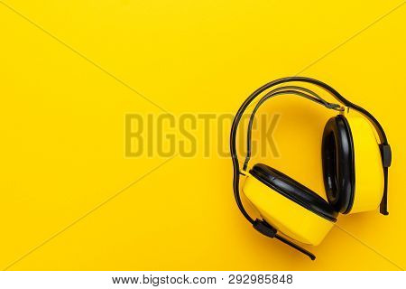 Hearing Protection Industrial Ear Muffs On Yellow Background. Top View Of Yellow Protective Ear Muff