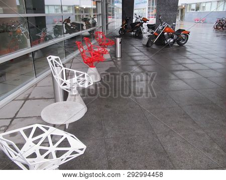 Open Space In Front Of The Shopping Center. Near The Building Are Chairs And Motorcycles. Modern Des