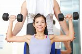 Gym fitness people - woman lifting weights with help from instructor and fitness trainer in gym. Beautiful smiling happy fit female fitness model training shoulders. poster