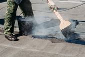 Worker repairs the roof with molten tar from a bucket with a broom. Roof repair tar. poster