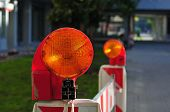 yellow reflector of a signal light at red white plastic boundary for temporary fencing poster
