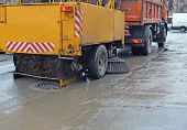 Road cleaning using a sweeper towed bya truck in rainy weather poster