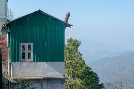 A Small Green Tin Or Metal Cabin High Up In The Mountains