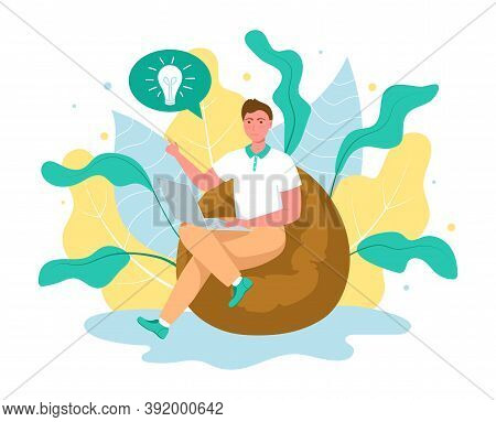 Cute Young Man Sitting On Comfy Frameless Chair With Laptop Computer. Concept Male Working Freelance
