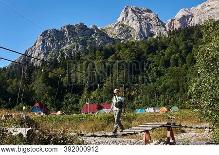 Young Woman Hiker Walks On A Hinged Bridge Across The River Against The Background Of A Campground I